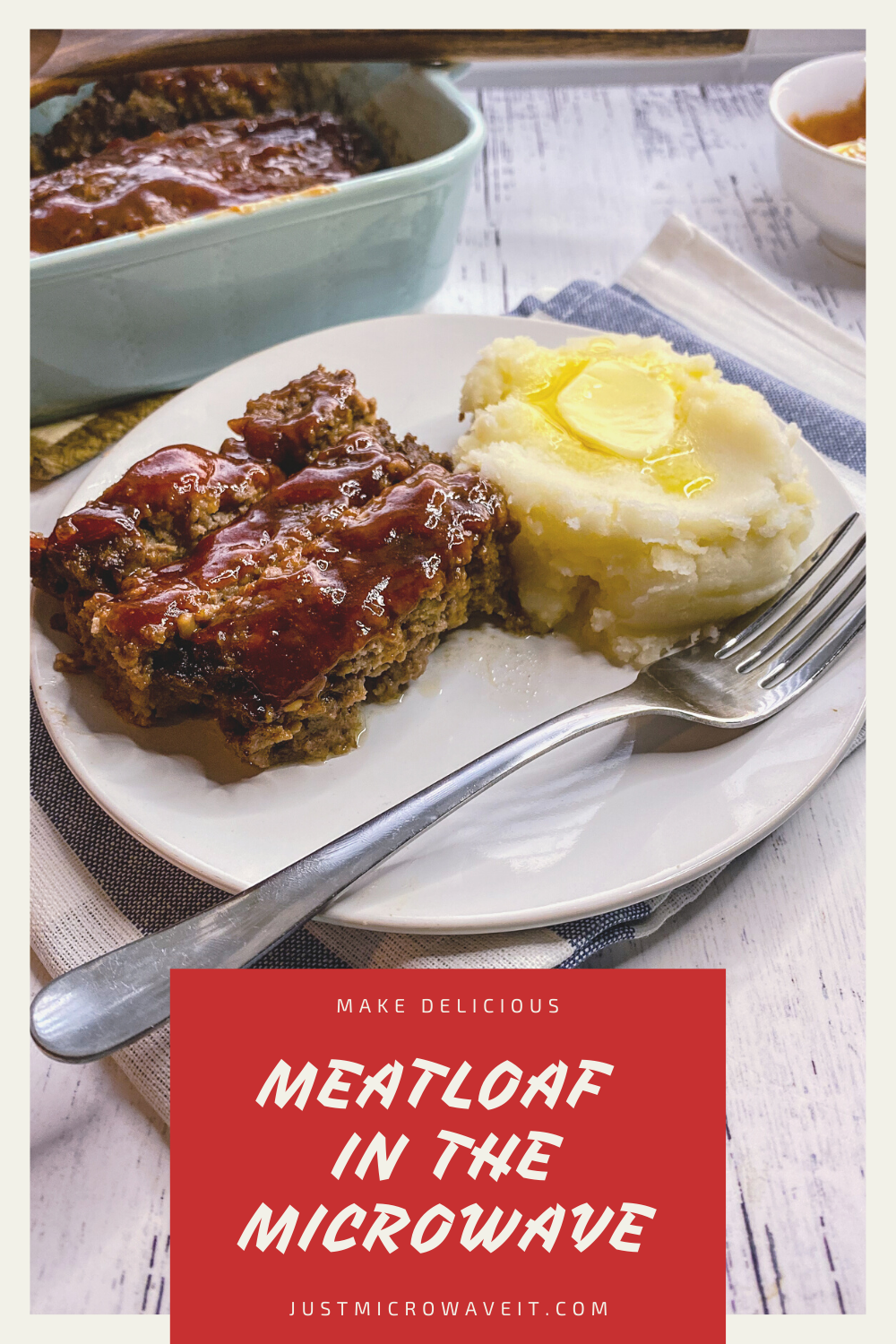 Close up view of three slices of meatloaf topped in meatloaf sauce next to a pile of mashed potatoes with melted butter on a white plate with fork. In the background is the baking dish full of more meatloaf.