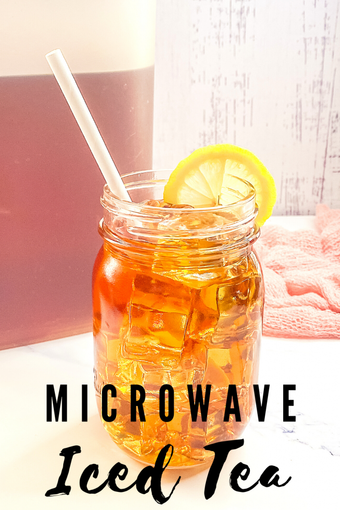 A mason jar glass full of ice and iced tea with a white straw with a pitcher of tea behind it.