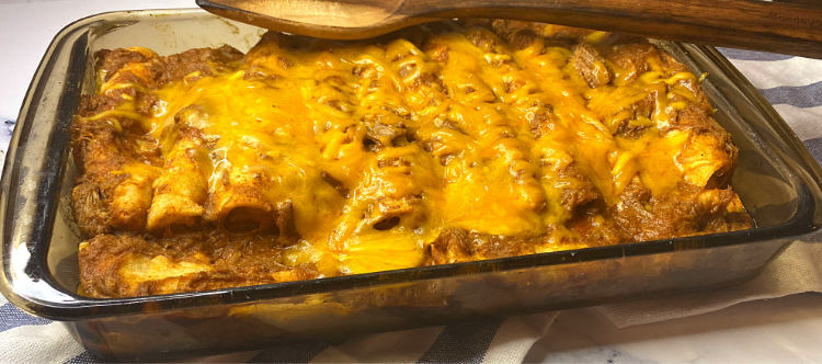 A pan full of chili con carne cheese enchiladas
