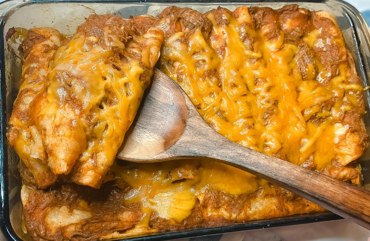 Top view of a spatula holding 3 chili con carne cheese enchiladas over a pan of enchiladas