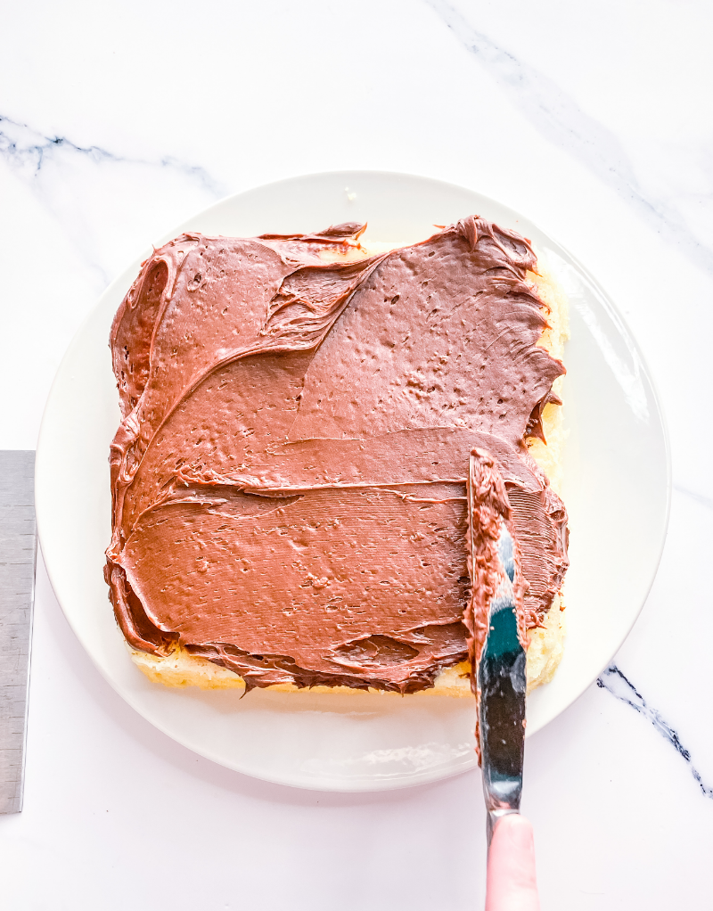 Frosting a yellow layer cake with chocolate frosting.