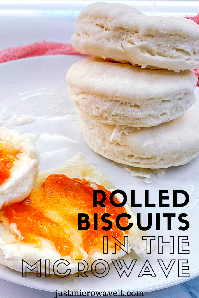 A stack of rolled biscuit and another biscuit on a white plate with apricot jam.