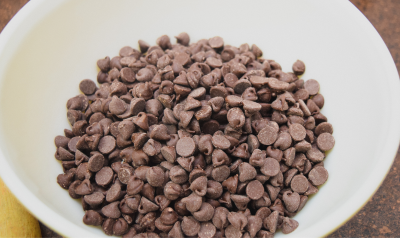 A white bowl of chocolate chips.
