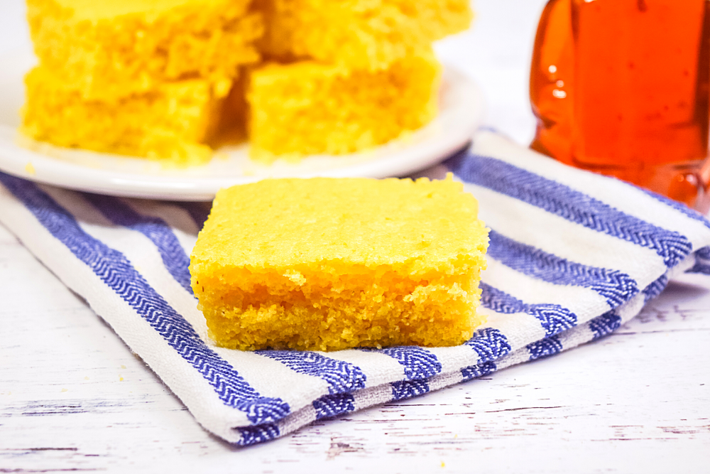 A single square of Microwave Cornbread on a blue striped towel with with a plate of cornbread behind it.