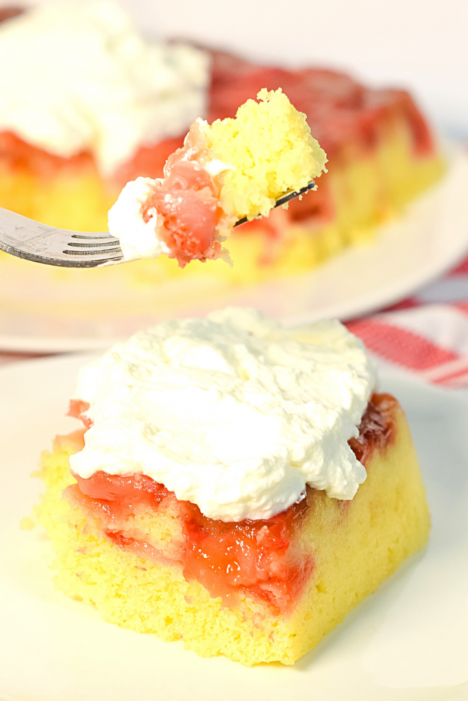 Close up of the microwave strawberry upside down cake with a fork holding a bite over it.